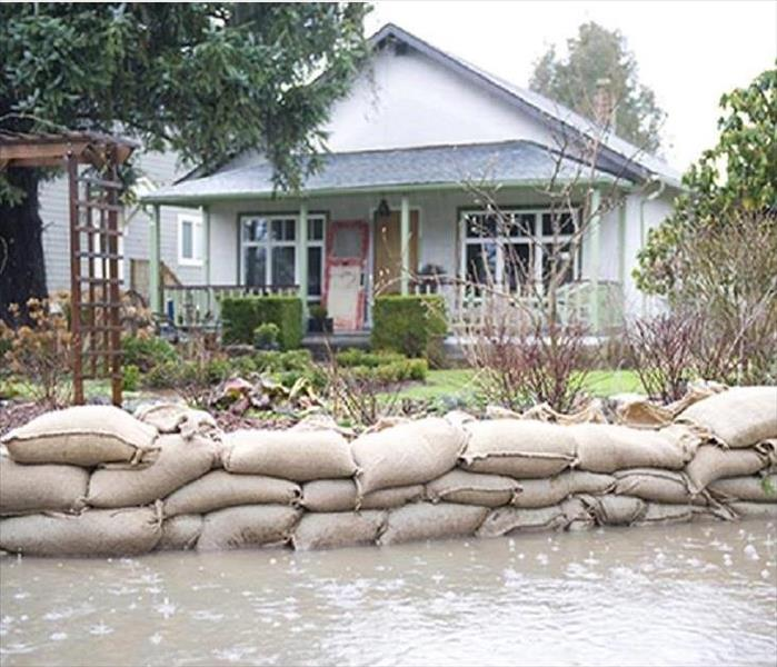 This picture shows sand bags stacked in front of a home protecting it from floodwaters.
