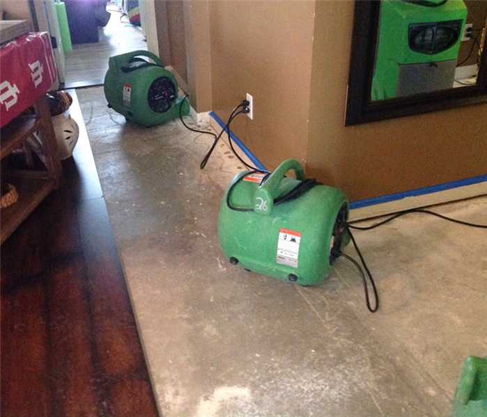This picture shows some air movers drying the wall after a water damage in a hallway.