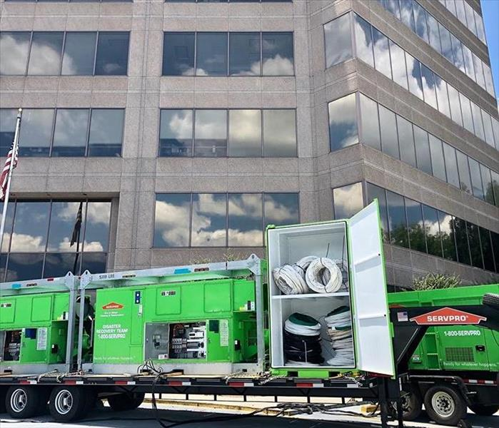 This picture shows a SERVPRO semi truck full of equipment parked in front of an office building.