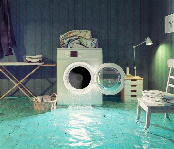 This picture is of a laundry room with water pouring out of the washer onto the floor.