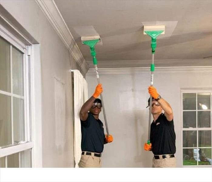 SERVPRO restoration professionals cleaning smoke from the ceiling.